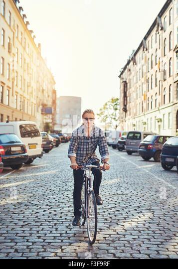 Mann sein Fahrrad durch die Stadt, lächelnd in die Kamera sieht cool Stockbild