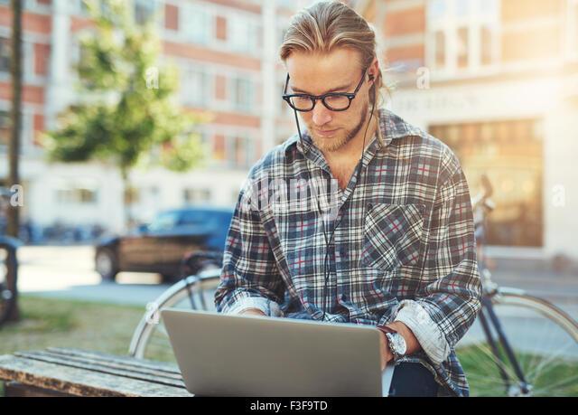Jungen Mann mit seinem Laptop draußen arbeiten konzentriert Stockbild