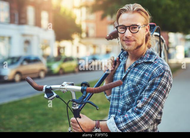 Porträt von blonden weißen Mann in der Stadt mit dem Fahrrad - Stock-Bilder