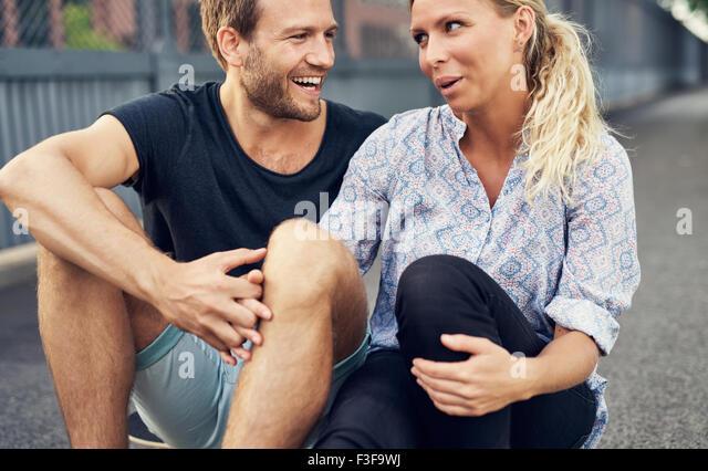 Paare, die haben einer guten Zeit beim Sitzen auf dem Boden Stockbild