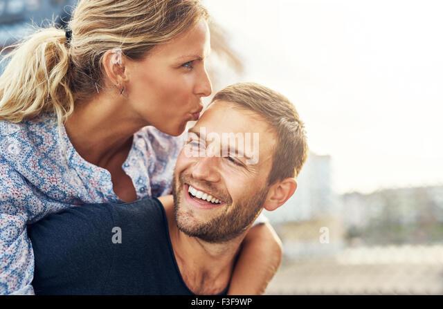 Frau Mann küssen, während er lacht, junges Paar - Stock-Bilder