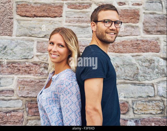 Glückliches Paar stehen Rücken an Rücken und lächelnd in die Kamera vor Brick Wall Hintergrund Stockbild