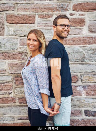 Drei Viertel Schuss von einem glücklichen jungen Paar zurück zu halten zurück, während ihre Stockbild