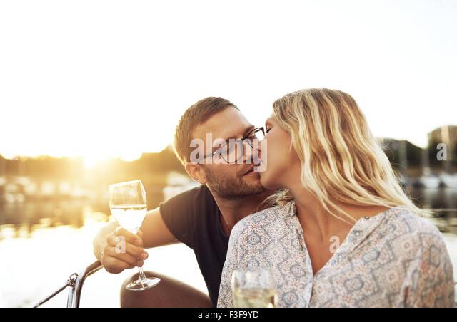 Mann und Frau küssen, sitzt auf einem Boot Stockbild