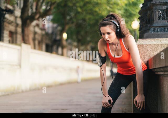Weibliche Läufer tragen von Kopfhörern eine Pause am Ufer Stockbild