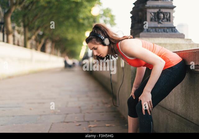 Junge weibliche Läufer tragen von Kopfhörern eine Pause am Ufer Stockbild