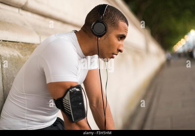 Erschöpft von männlichen Läufer tragen von Kopfhörern eine Pause am Ufer Stockbild