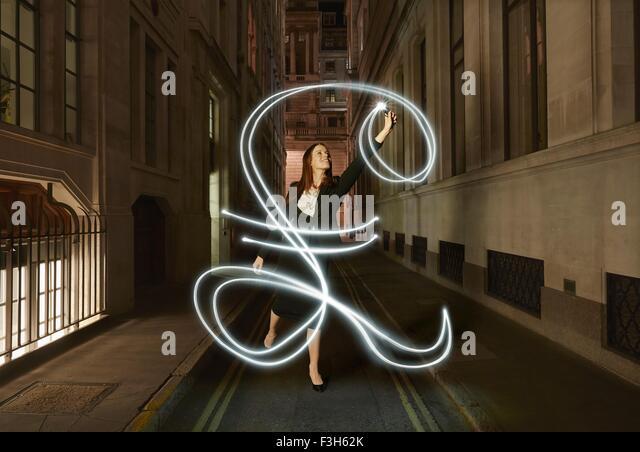 Geschäftsfrau Lichtmalerei glühende Pfund anmelden Stadtstraße in der Nacht Stockbild