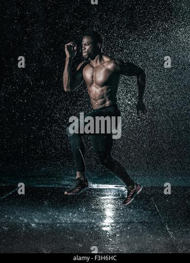 Mitte erwachsenen Mannes laufen im Freien, in Regen Stockbild