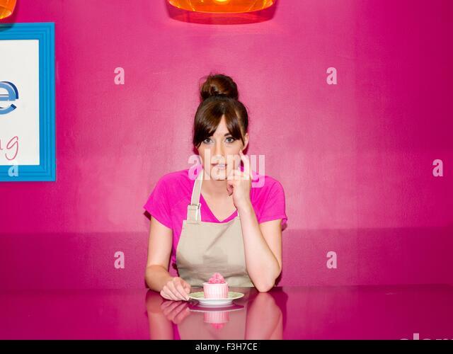 Junge Frau, arbeiten in der Konditorei mit Cupcake vor ihr sitzt Stockbild