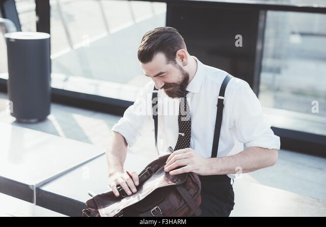 Stilvolle Geschäftsmann Eröffnung Aktenkoffer auf Stadt Sitz Stockbild