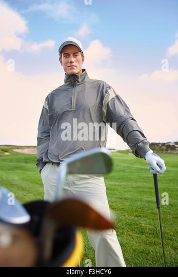 Golfer halten gold Club, Hand in der Tasche, Blick in die Kamera Stockbild
