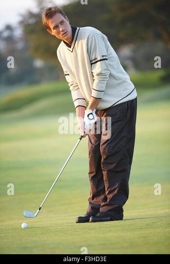 Golfer halten Golf Club gold Schaukel nehmen Vorbereitung wegschauen Stockbild