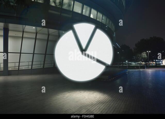 Glühende Kreisdiagramm-Symbol in der Stadt bei Nacht Stockbild