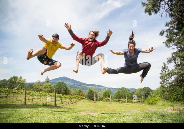 Drei Erwachsene springen in ländlicher Umgebung, Mitte Luft, lachen Stockbild
