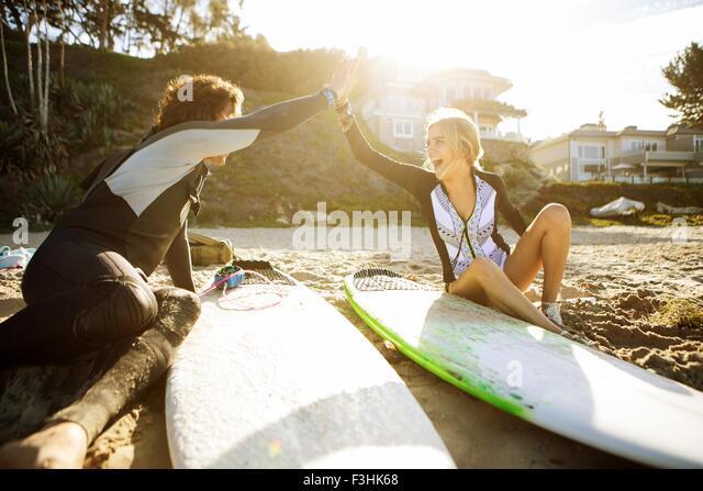 Paar am Strand sitzen, Hände klatschten in high five, Surfbretter neben Ihnen Stockbild