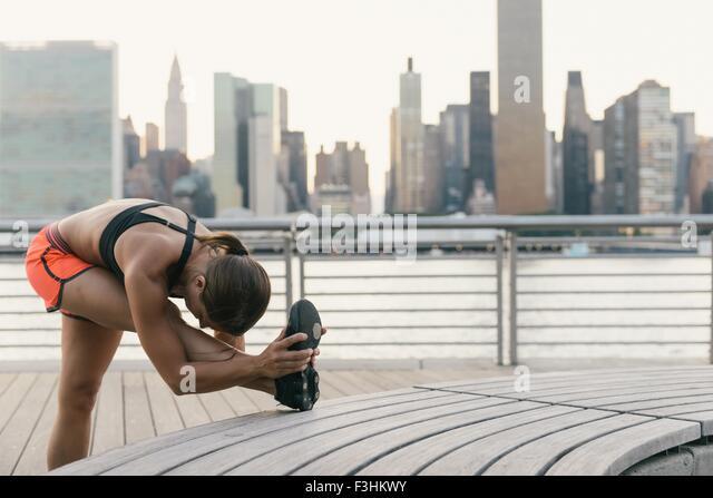 Junge Frau in Laufbekleidung neben Fluss stretching vor dem Training Stockbild