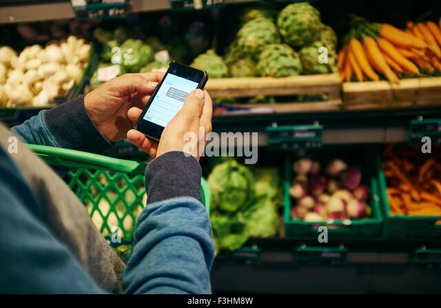 Mann einkaufen und mit Smartphone in Supermarkt Stockbild