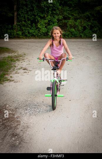 Vorderansicht des Mädchens balancieren auf Fahrrad, Beine angehoben, Blick auf die Kamera zu Lächeln Stockbild