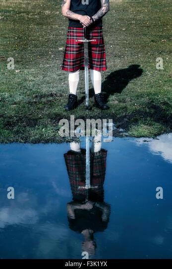 ein Schotte mit seinem Schwert in die Reflexion von einem Teich zu sehen Stockbild