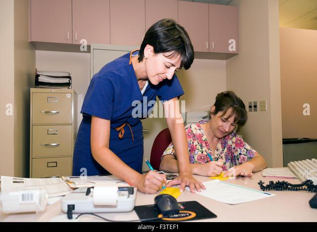 Weiblichen Arzt und Angestellte an der Rezeption im Büro zusammenarbeiten. Herr © Myrleen Pearson Stockbild