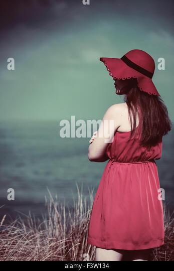 Junge Frau in einem roten Kleid am Strand Stockbild