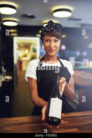 Lächelnde junge Kellnerin mit einer Flasche Wein an einen Kunden zur Genehmigung, bevor Sie es öffnen, Stockbild