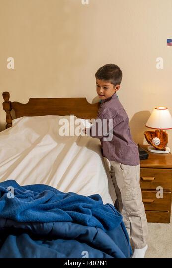 Ordentlich 7-10 jährige Olds Young Korean/American Boy sein Bett machen.   Herr © Myrleen Pearson Stockbild