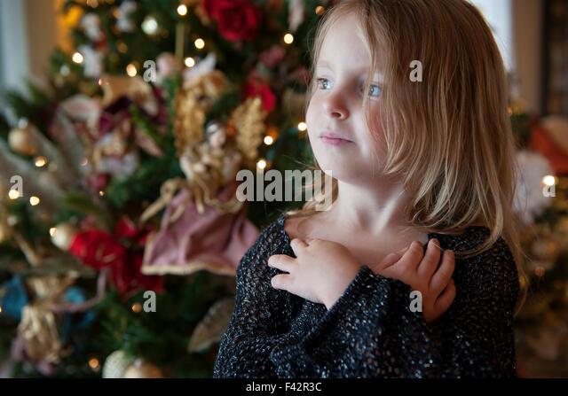 Mädchen träumen mit Weihnachtsbaum im Hintergrund Stockbild