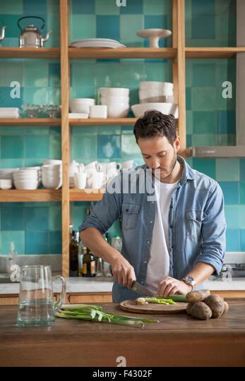 Mann schneiden Zutaten in Küche Stockbild