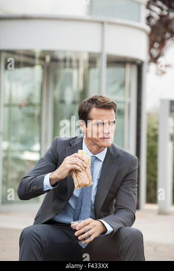 Geschäftsmann mit Mittagessen im freien Stockbild
