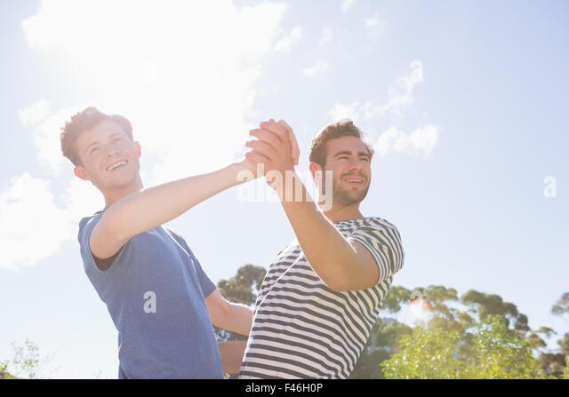 Glückliche homosexuelle Paare tanzen im Garten Stockbild