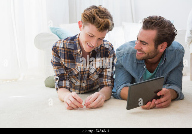 Froh, dass homosexuelle Paare am Boden liegend und mit tablet PC Stockbild
