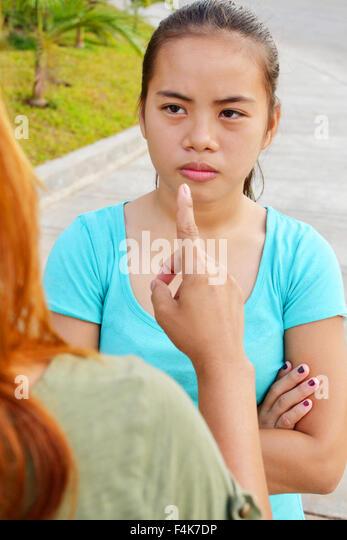 Asiatische Teenager suchen wütend auf ihre Mutter mit ihr zu streiten und ein Fingerzeig Stockbild