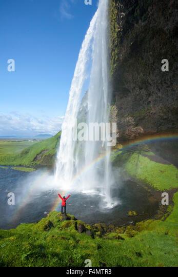 Person und Regenbogen unter 60m hohen Seljalandsfoss Wasserfall, Sudhurland, Island. Stockbild