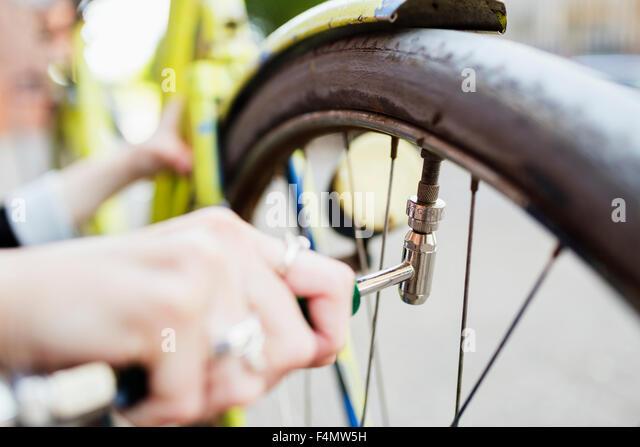 Bild der Frau die Hand aufblasende Fahrradreifen auf Bürgersteig beschnitten Stockbild
