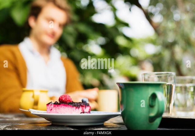 Kuchen und Kaffee am Tisch mit Mann sitzt im Hintergrund Stockbild
