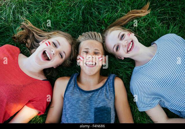 Österreich, drei Jugendliche mit nationalen Farben gemalt auf ihren Wangen, auf einer Wiese liegend Stockbild