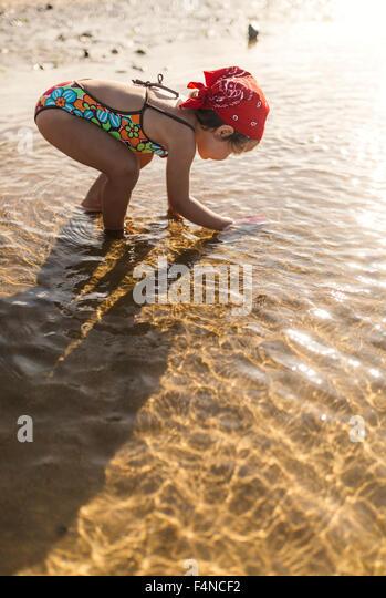 Kleines Mädchen spielt am Strand Stockbild