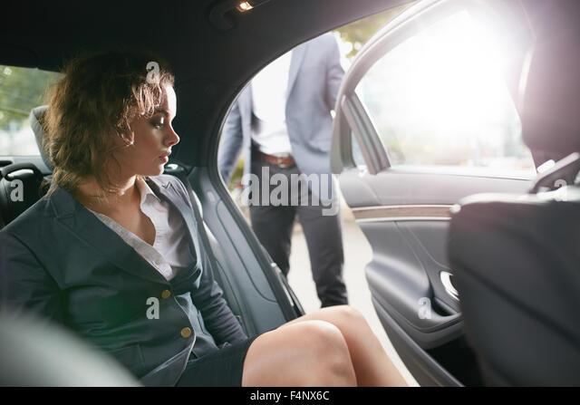 Man öffnet eine Beifahrertür für eine Geschäftsfrau aus einem Auto. Unternehmerin, die Reisen Stockbild