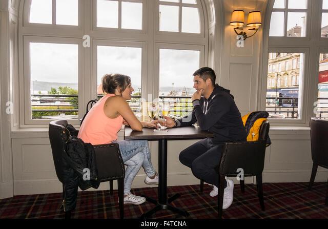 Junges Paar Hand in Hand mit ernsthaften Gespräch im Pub in Argyll Hotel, Dunoon, Schottland.   © Myrleen Stockbild