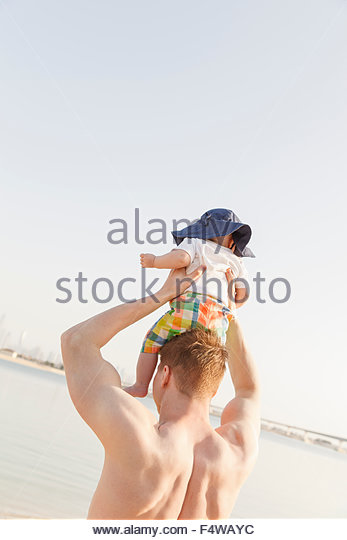 Man Betrieb Sohn (12-17 Monate) am Strand Stockbild