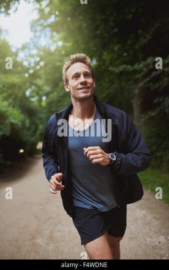 Gesunde junge Mann joggen durch den Park an einem sonnigen Morgen tun, seine tägliche Schulung und Training, Stockbild