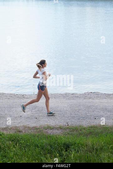 Finnland, Uusimaa, Espoo, Teenage Mädchen (16-17) Seeufer entlang joggen Stockbild