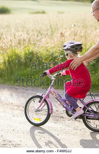 Mellersta Finnland Jyväskylä, Mann auf der Suche nach Mädchen (2-3) am Fahrrad Stockbild