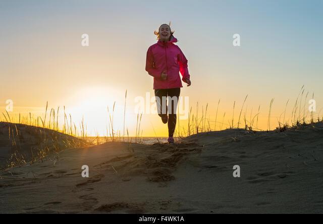 Finnland, Pohjanmaa, Pietarsaari, Faboda, junge Frau, Joggen am Strand bei Sonnenuntergang Stockbild
