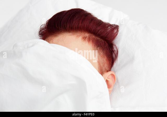 Rothaarige Kopf im Bett auf weißen Kissen Bettwäsche fallenden Stockbild