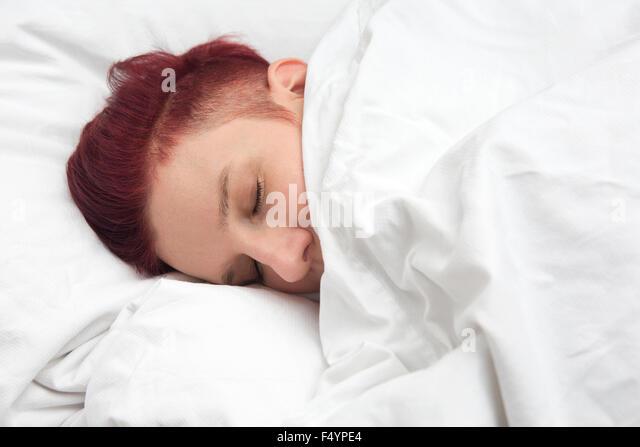 rothaarige Frau schläft im Bett auf weißer Bettwäsche Stockbild