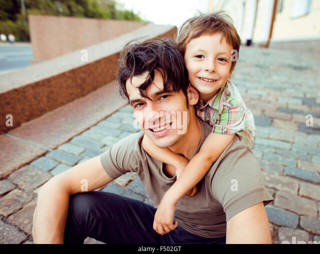 kleinen Sohn mit Vater in der Stadt Hagging und lächelnd, casual look Stockbild