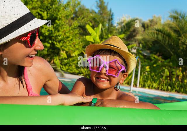 Glückliche Mutter und jungen tragen von Sonnenbrillen im pool Stockbild